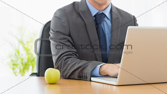 Smartly dressed businessman with laptop at office