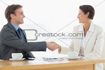 Smartly dressed couple shaking hands in business meeting