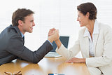 Smiling business couple arm wrestling at office desk