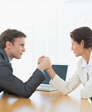 Business couple arm wrestling at office desk