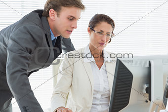 Smartly dressed business couple using computer
