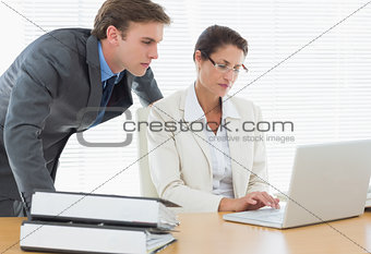 Business couple using laptop at office desk