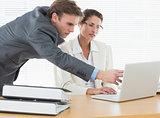 Concentrated business couple using laptop