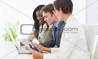 Business colleagues using laptop and digital tablet at desk