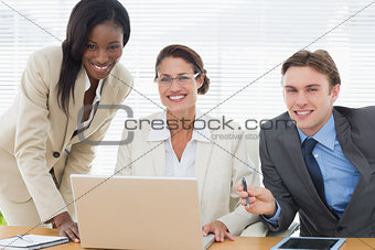 Smiling business colleagues with laptop in meeting
