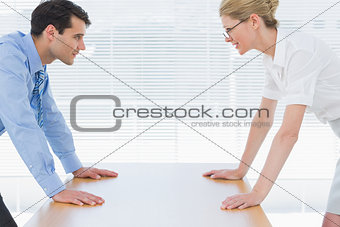 Smiling business couple looking at each other with palms at desk