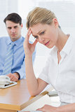 Upset businesswoman with man working on laptop