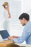 Businesswoman and man using cellphone and laptop at office