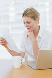 Businesswoman reading a document besides laptop at desk