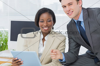 Business colleagues using digital tablet in office