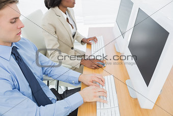 Business colleagues using computers at desk