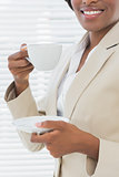 Mid section of smiling businesswoman with a cup of tea