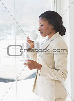 Businesswoman with tea cup looking through office window