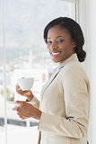 Elegant smiling businesswoman with a cup of tea in office