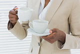 Mid section of elegant businesswoman with tea cup