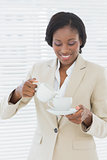 Elegant smiling businesswoman with tea cup in office