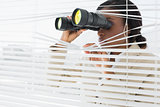 Businesswoman peeking with binoculars through blinds