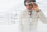 Businesswoman peeking through blinds