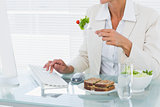 Businesswoman using computer while eating salad at desk