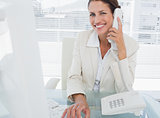 Smiling businesswoman using computer and phone