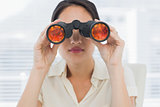 Closeup of a businesswoman looking through binoculars