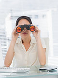 Businesswoman looking through binoculars at desk