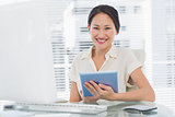 Smiling businesswoman using digital tablet at desk