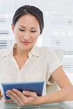 Businesswoman using digital tablet at desk