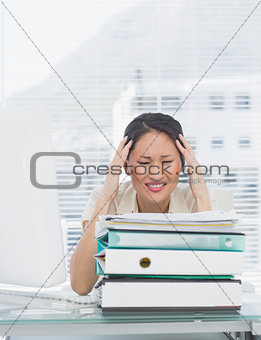 Angry businesswoman with stack of folders at desk