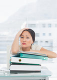 Bored businesswoman with stack of folders at desk