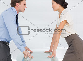 Business couple looking at each other with palms at desk