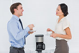 Business couple with tea cups chatting in office