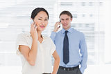 Businesswoman and man using cellphones in office