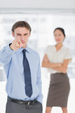 Businessman pointing towards camera with woman in office
