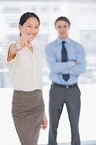 Businesswoman pointing towards the camera with man in office