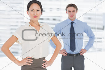 Business colleagues with hands on hips in office