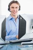 Male executive with headset using computer at desk