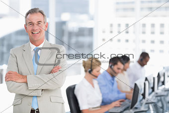 Happy businessman with executives using computers in office
