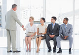 Businessman shaking hands with woman by people waiting for interview