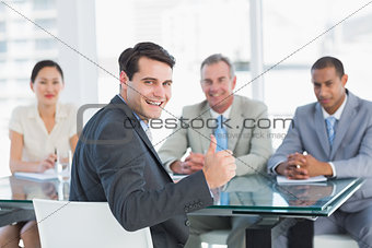 Executive gesturing thumbs up with recruiters during job interview