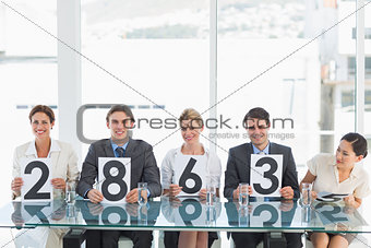 Group of panel judges holding score signs