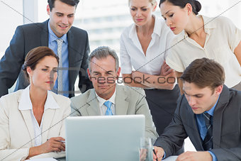 Business colleagues with laptop at desk