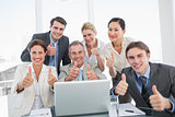 Business colleagues with laptop gesturing thumbs up at desk