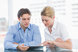 Businessman and woman using digital tablet in office