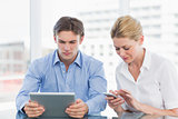 Businessman and woman using digital tablet and cellphone at office