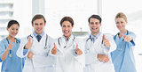 Cheerful doctors gesturing thumbs up at hospital