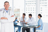 Doctor with group around table in background at hospital