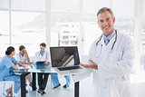 Doctor holding laptop with group around table in hospital