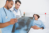 Doctors examining xray by patient in hospital
