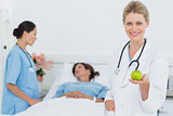 Smiling doctor holding apple with patient in hospital